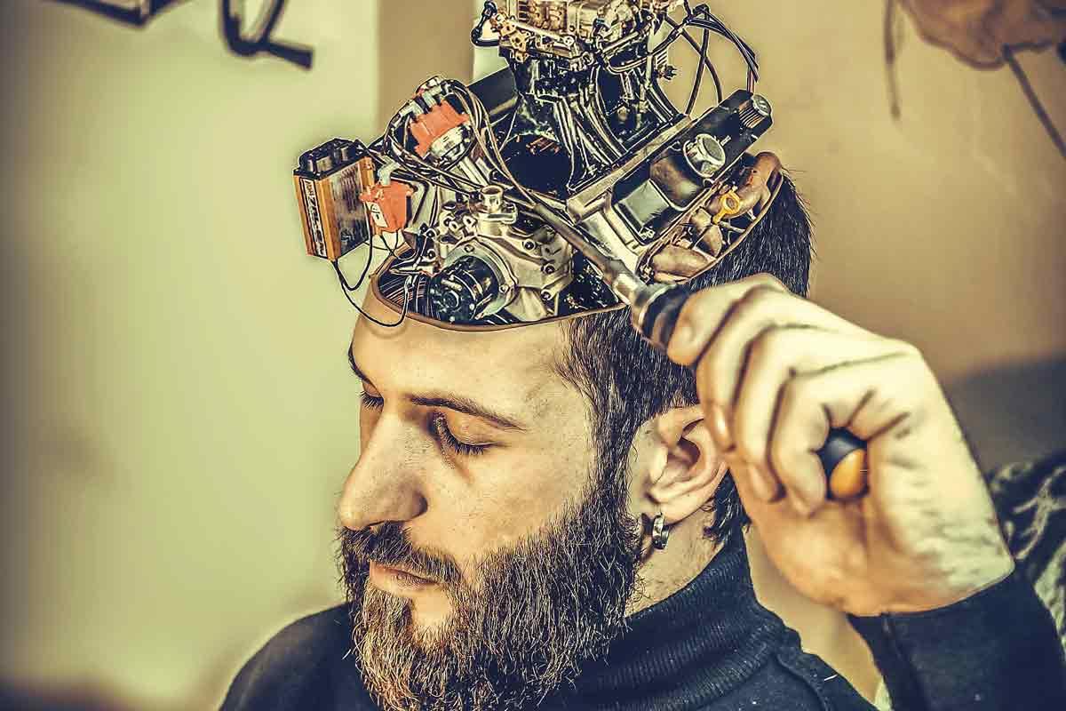 Mann schraubt mit Schraubenzieher an seinem offen Gehirn herum, das voller Technik steckt