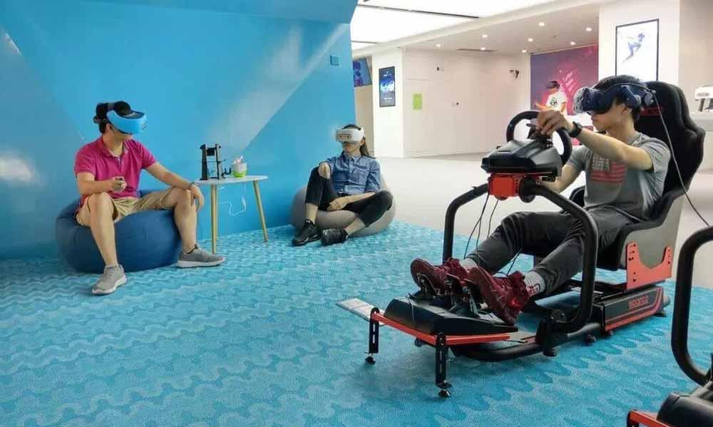 Vive Pro im Rennsimulator und zwei Focus-VR-Hipster. Bild: HTC
