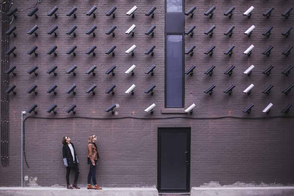 EIne Wand voller Kameras beobachten zwei Personen