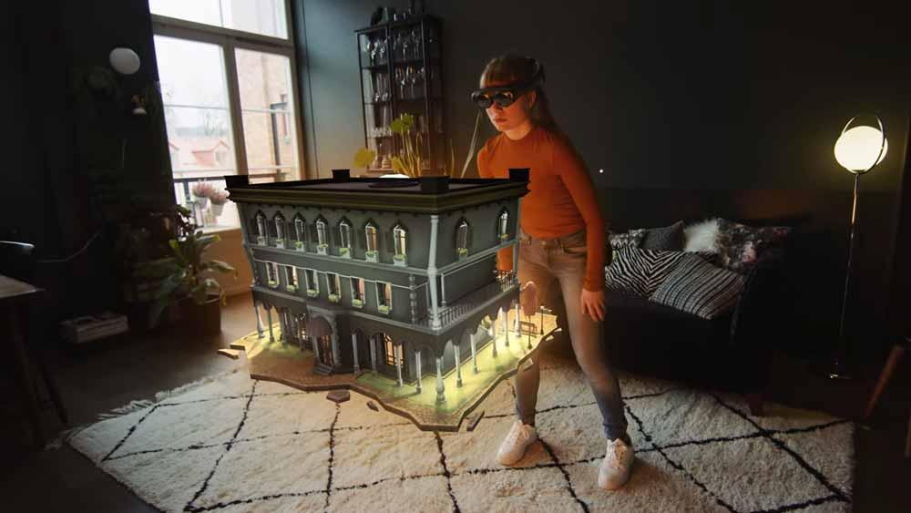 Eine Frau steht im Raum und betrachtet ein Hologramm eines Hotels