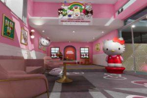 Ein virtueller Raum mit einer Hello-Kitty-Katze, pinken Wänden und einer bequemen Wohnzimmereinrichtung.