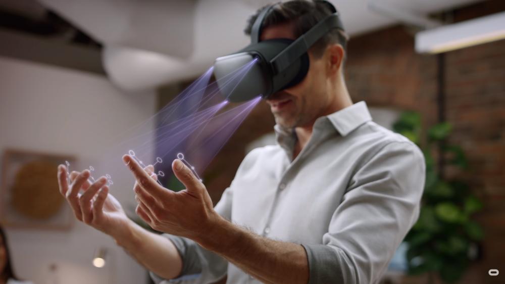 Ein Mann trägt eine Oculus Quest VR-Brille. Er hält seine Hände vor die VR-Brille, die sie mit ihren Frontkameras erfasst (Handtracking).