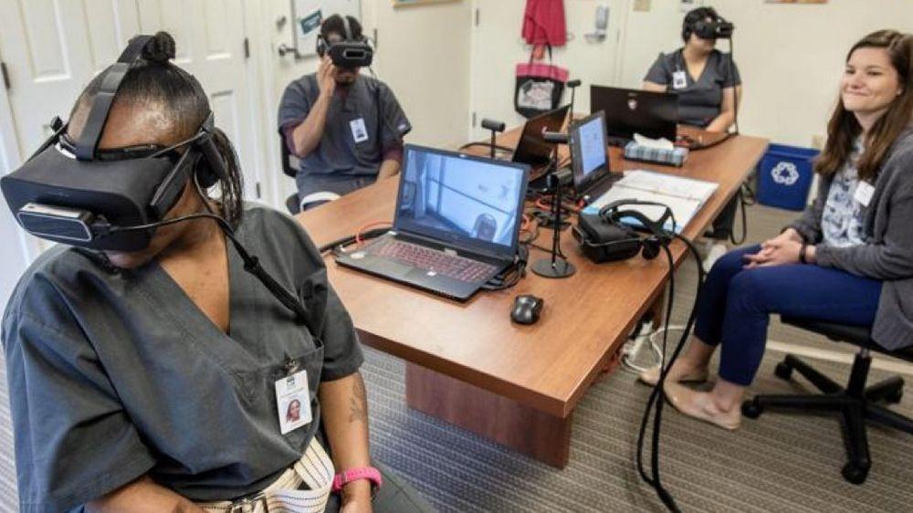 Mehrere Personen mit VR-brillen auf dem Kopf sitzen um einen Tisch herum und nutzen ein VR-Trainingsprogramm von Embodied Labs