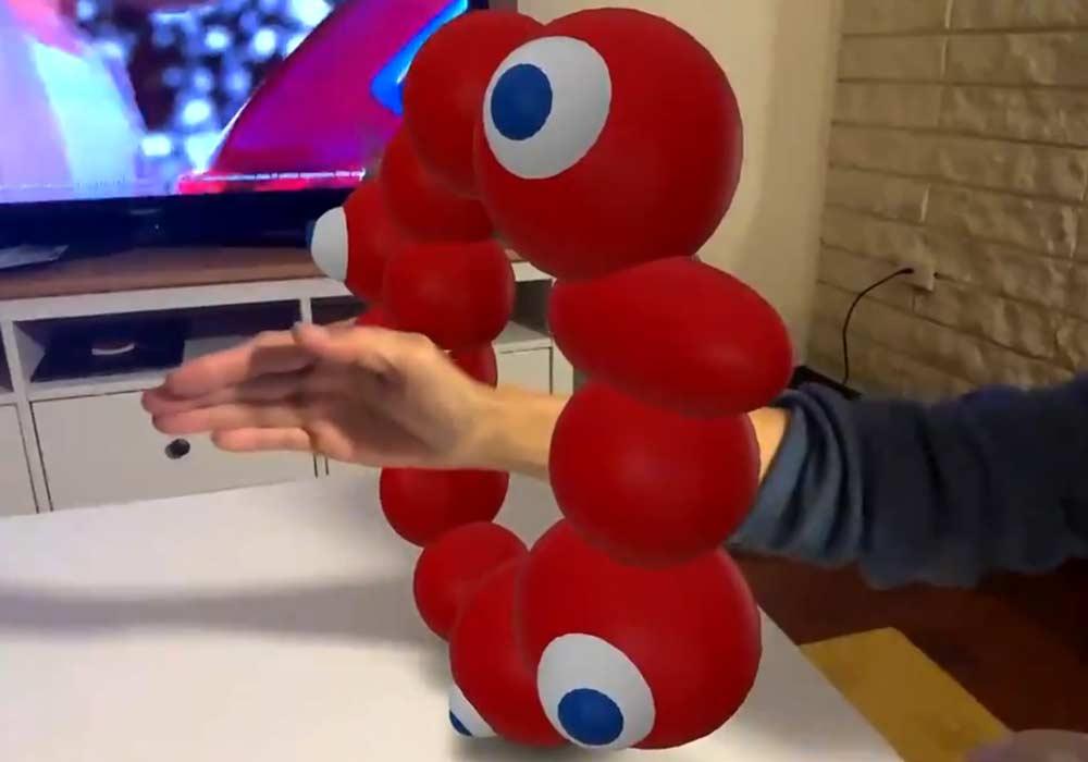 Apples AR-Technik wird immer realistischer. Ein digitales Objekt verdeckt eine reale Hand in Bewegung.