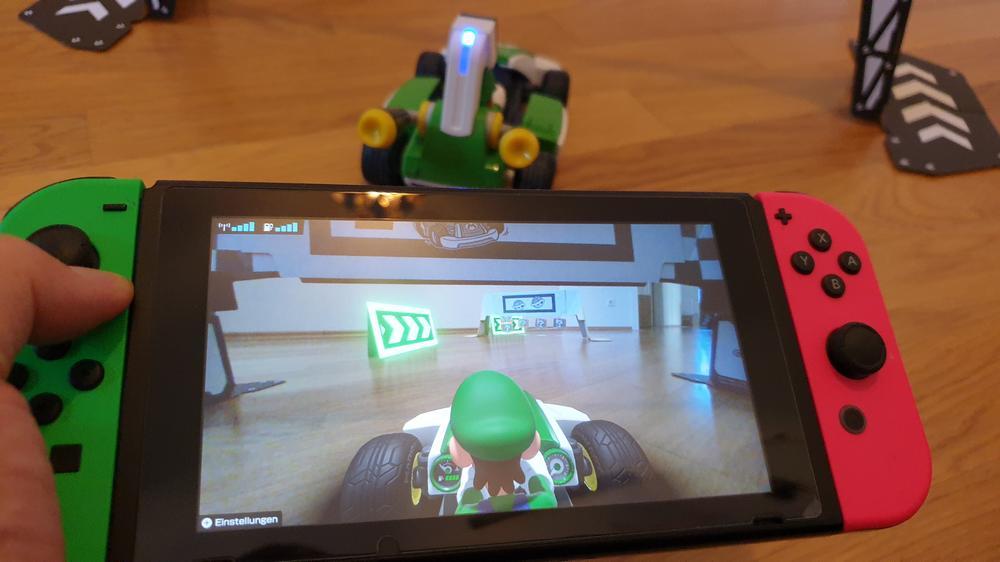 Ansicht des Wagens, der Tore und Begrenzeungen sowie der AR-Objekte auf dem Switch-Bildschirm, dahinter die realen Objekte