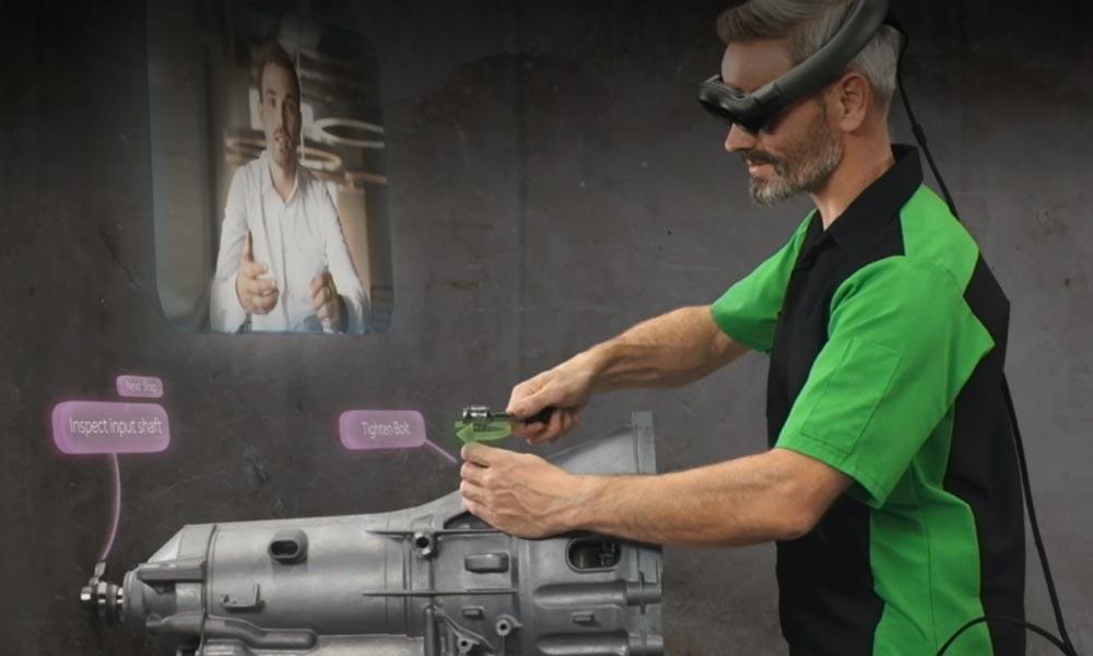 Ein Mann trägt die AR-Brille Magic Leap. Er betrachtet ein reales Maschinenteil, auf dem er eine digitale Anleitung erkennt durch die AR-Brille.