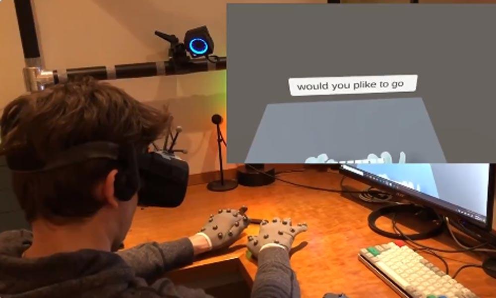 Ein Mann tippt mit Trackinghandschuhen auf einer unsichtbaren Tastatur auf seinem Schreibtisch.