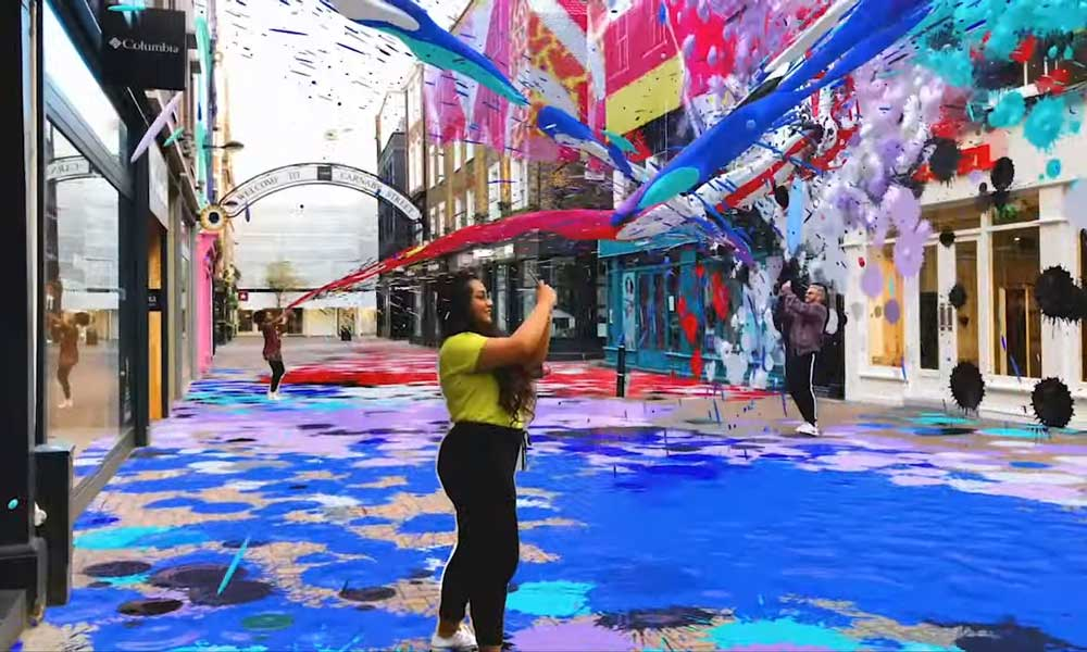 Menschen sprühen mit einer Smartphone-App digitale Farbe an Hauswände.