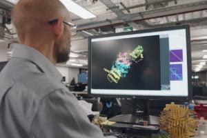 Ein Mann betrachtet auf einem Monitor eine Proteinfaltung.