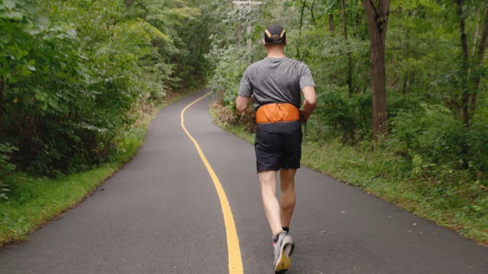 Ein blinder Mann läuft ohne Hund oder Helfer entlang einer Linie eine Straße entlang.