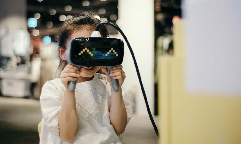 Ein kleines Mädchen hält sich eine VR-Brille vor das Gesicht und lacht dabei.