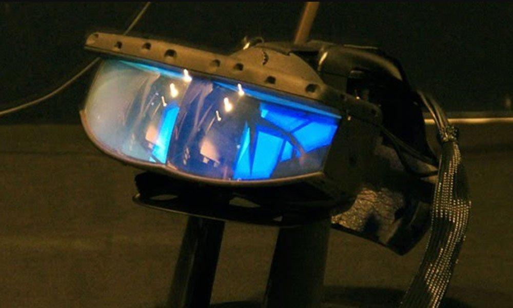 Eine VR-Brille mit durchsichtigem Display steht auf einem Ständer am Boden und schimmert blau.