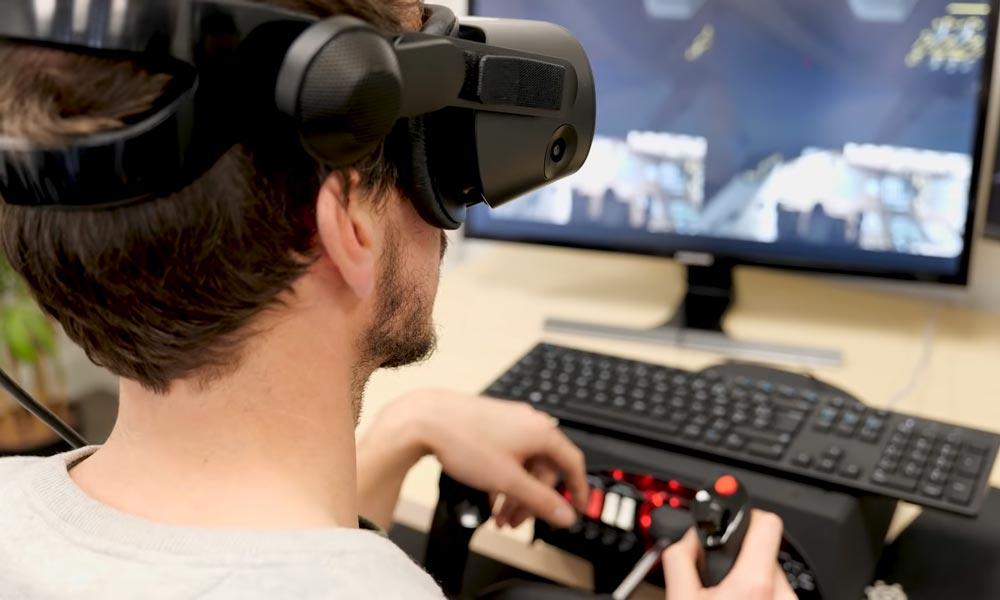 Mann mit VR-Brille sitzt vor Monitor