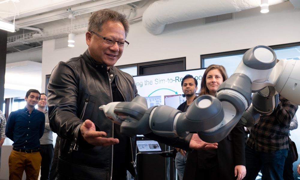 Nvidia-Chef Jensen Huang steht vor einem Roboterarm