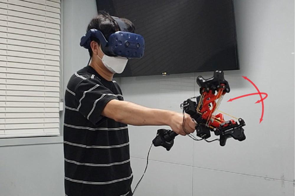 Ein Mann mit VR-Brille demonstriert einen aufwendigen Haptik-VR-Controller