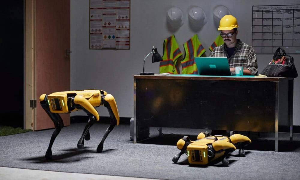 Zwei Hunderoboter Spot stehen und liegen vor einem Schreibtisch in einem Büro. Am Schreibtisch sitzt ein Mann und arbeitet am Notebook.