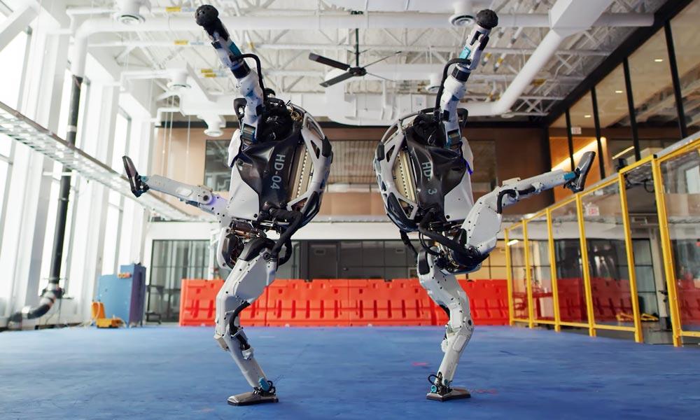 Zwei humanoide Roboter Atlas tanzen zusammen und machen einen großen Ausfallschritt.