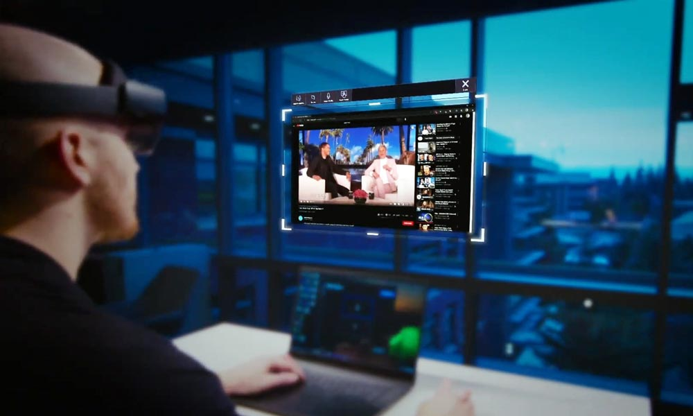 Ein Mann schaut mit einer AR-Brille auf einen digitalen Monitor.