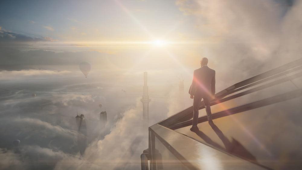 Agent 47 hoch oben auf einem Skyscraper mit Blick über die Wollen in Hitman 3