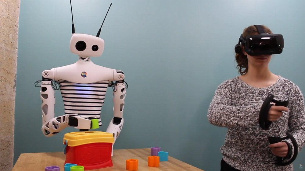 Roboter Reachy wird von einer Frau mittels VR-Brille und VR-Controllern gesteuert
