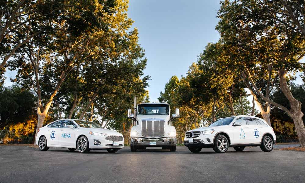 Zwei weiße Autos und ein weißer Truck mit Lidar-Sensor stehen im Halbkreis.