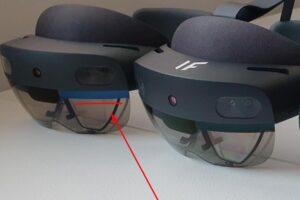 Zwei Hololens 2 Brillen liegen auf einem Tisch. Die neue hat einen blauen Balken über den Linsen, die alte einen schwarzen.