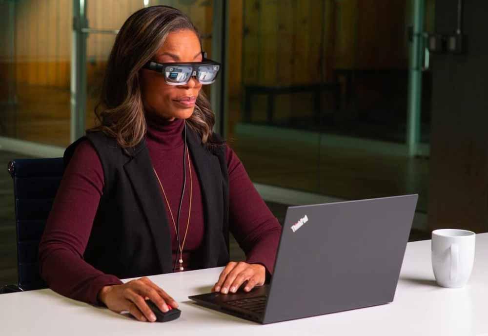 EIne Frau sitzt mit einer AR-Brille vor einem Notebook und schaut auf den Monitor.