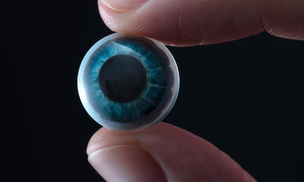 Eine AR-Kontaktlinse wird zwischen zwei Fingern groß vor die Kamera gehalten.