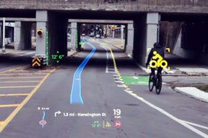 Eine Straßenszene mit Brücke und Fahrradfahrer rechts. Das AR Hud zeigt den Weg auf der Straße an, erkennt die Höhe der Brücke und den Fahrradfahrer rechts.