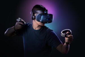 Ein Mann trägt die VR-Brille Vive Cosmos von HTC und hält dabei zwei Controller in der Hand.