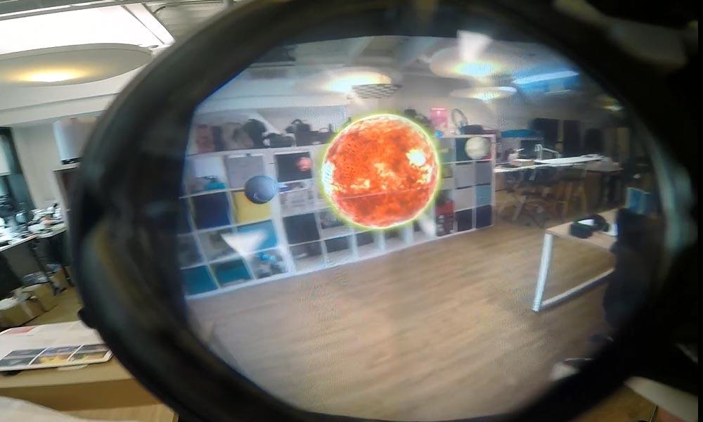 Durch die Linse sieht man ein digitales Planetensystem, das im Raum schwebt.