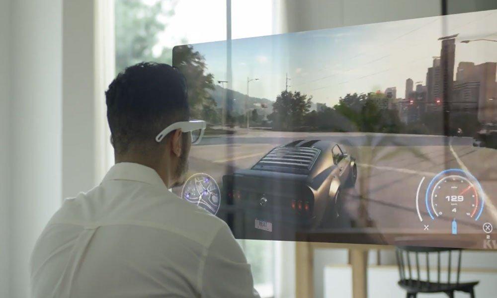 Ein Mann schaut durch eine Display-Brille auf einen digitalen Monitor, auf dem ein Videospiel läuft.