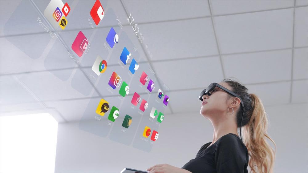Frau mit AR-Brille Nreal Light schaut durch die Brille auf App-Übersicht im Raum