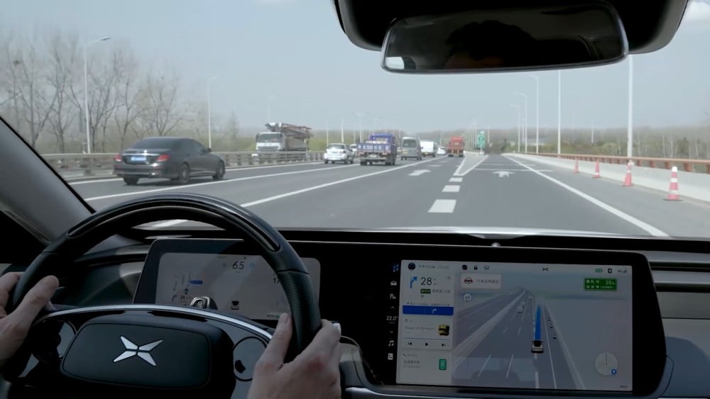 Der Blick durch das Cockpit eines autonom fahrenden Xpeng P7 auf einem chinesischen Highway.
