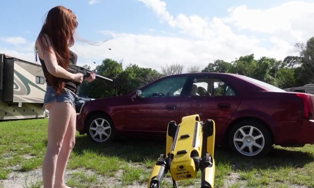 Eine Frau mit Maschinengewehr und einem Hunderoboter von Boston Dynamics