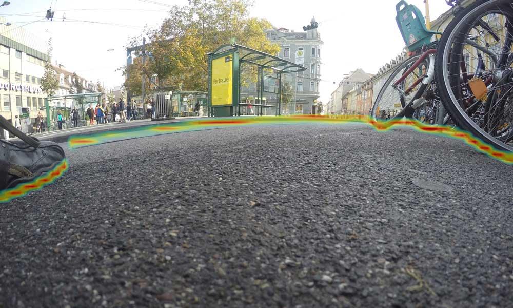 Eine Kameraaufnahme aus der Schuhperspektive: farblich eingegrenzt ist der gefahrlos begehbare Bereich, erkannt und interpretiert durch den Bilderkennungsalgorithmus der TU Graz.   Bild: TU Graz