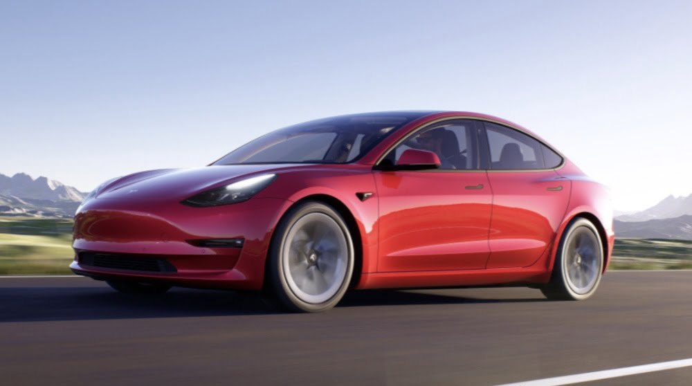 Teslas Model 3 in rot fährt über eine Straße.