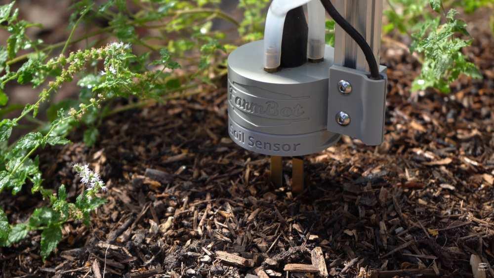 Der Gärtnerroboter FarmBot säht Gemüse in einem Beet.