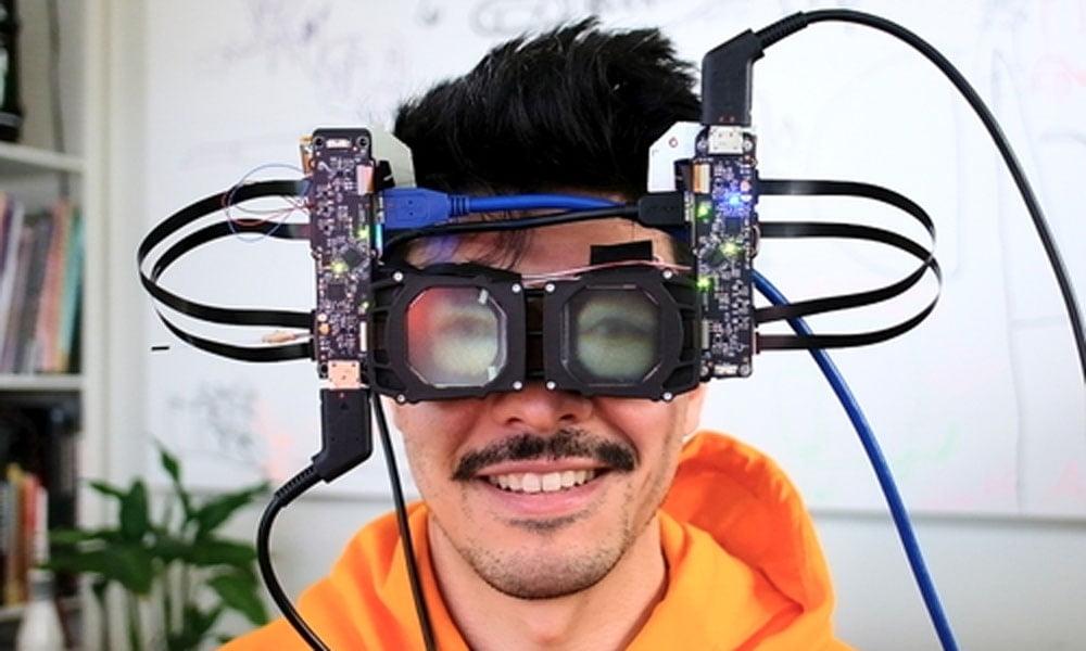 Ein Mensch sitzt mit einer VR-Brille ohne Außenhülle vor der Kamera. Auf den beiden Displays sind außen virtuelle Augen aufgebracht.
