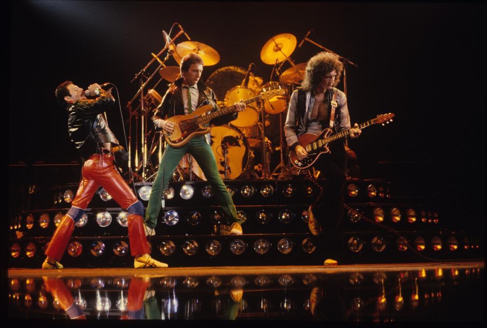 Eine Werbebild für ein Alexa Skill, das die Rockband Queen auf einer Bühne zeigt.
