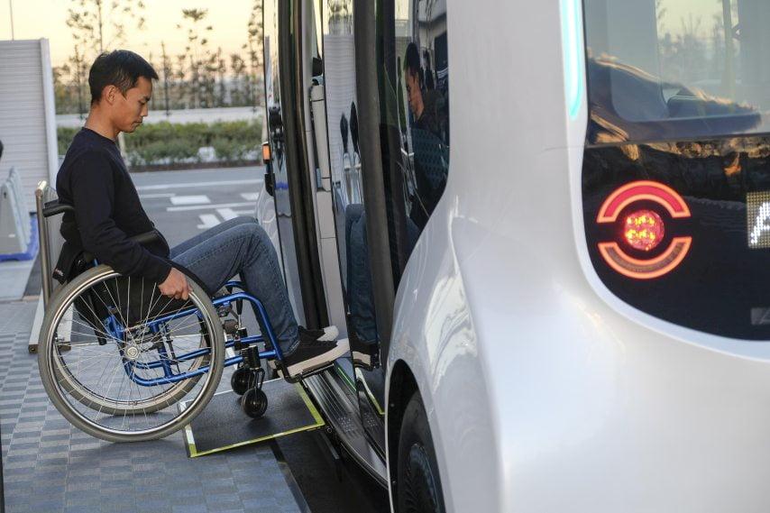 Ein Rollstuhlfahrer fährt in einen autonom fahrenden Toyota e-Palette Kleinbus.