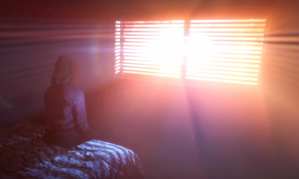 Eine Frau sitzt vor einem Fenster und schaut hinaus. Im Zimmer ist es dunkel, helles Licht kommt durch das Fenster.