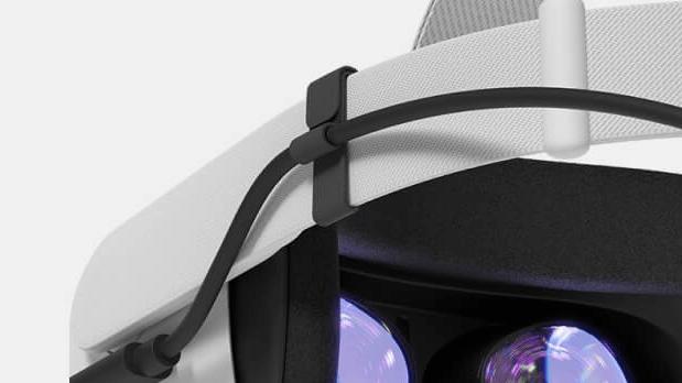 Blick auf das seitliche Kopfband der Oculus Quest 2, an dem mit einer Halterung das Link-Kabel angebracht ist