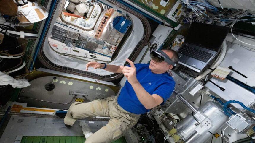 Der japanische Astronaut Noguchi schwebt schwerelos bei der Laufband-Wartung: Dank der AR-Brille auf dem Kopf sieht er die Anleitung direkt im Blickfeld und auf dem zu wartenden Gerät.