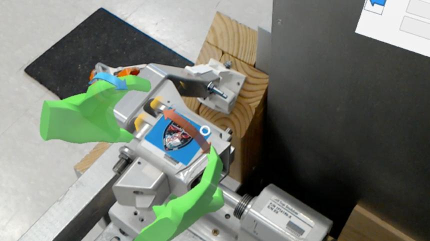 Über einem Gerät erscheint eine digitale Einblendung, die Arbeitsschritte für eine Wartung darstellt.