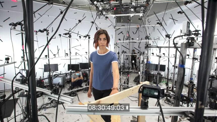 Eine Frau steht in einem Käfig voller Kameras.
