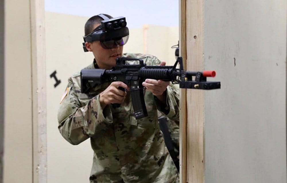 Ein Soldat trägt eine große AR-Brille auf dem Kopf und legt ein Gewehr an.