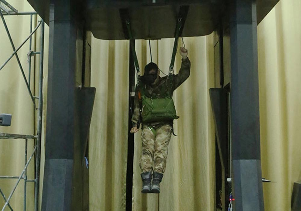 Ein Soldat mit VR-Brille hängt an Seilen in einer großen Maschine.