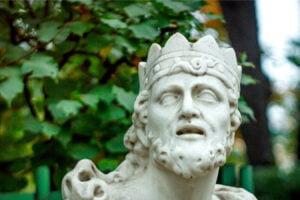 Gekrönte Marmorstatue vor Laubwerk