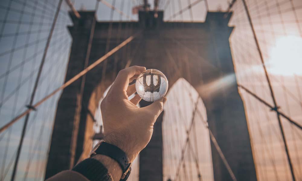 Ein Mann schaut durch ein Glas auf ein Brückentor, das im Glas umgedreht erscheint.